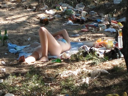 Woman sunbathing amongst rubbish